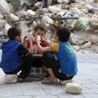 Aleppo sotto attacco: i bimbi giocano a carte tra le macerie