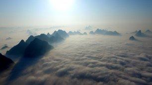 """In Cina il mondo è """"capovolto""""  tra le montagne  un mare di nuvole"""
