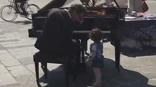 Il concerto è in strada: la bimba arriva e suona con il pianista