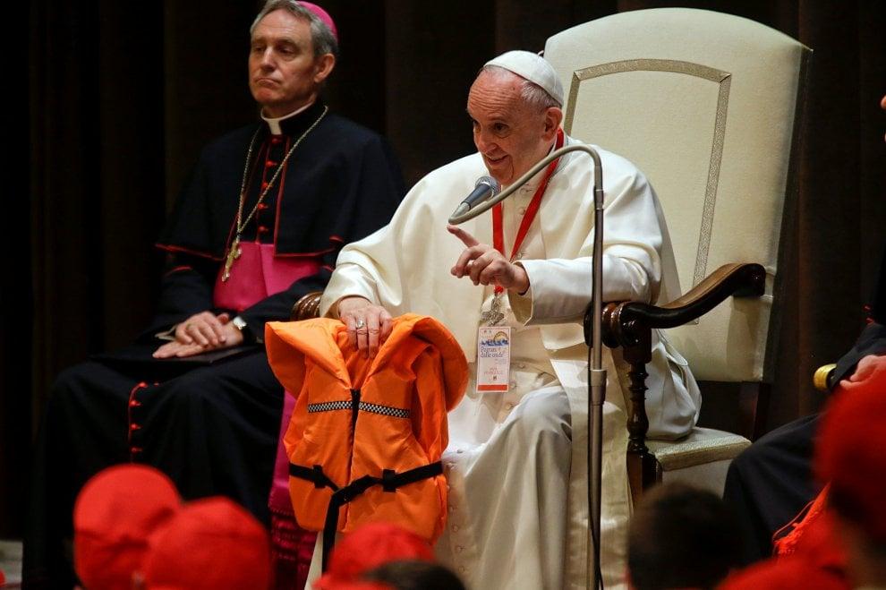 Papa Francesco mostra ai bambini il salvagente di una piccola profuga morta in mare