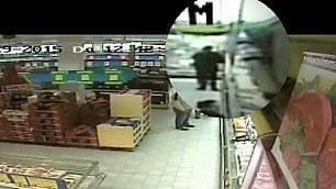 Vigile in divisa ruba salame  e parmigiano in un supermercato