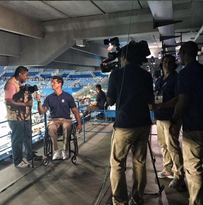 Entrevista com o fotógrafo João Maia pelo paratleta e apresentador Fernando Fernandes. Equipe de filmagem a direita em primeiro plano. A esquerda o Fernando entrevista o João com a pista de atletismo do Engenhão ao fundo.