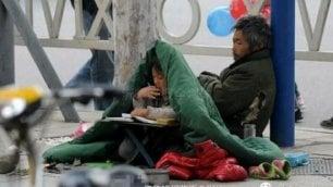 La bambina fa i compiti in strada   mentre il papà chiede l'elemosina