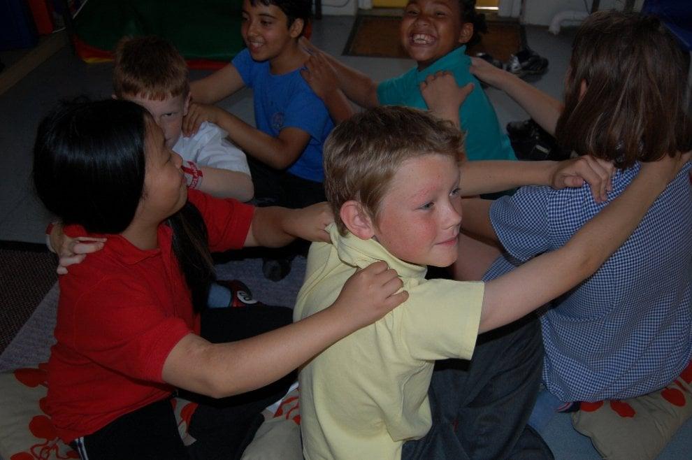 Bambini in classe imparano a massaggiare il compagno di banco