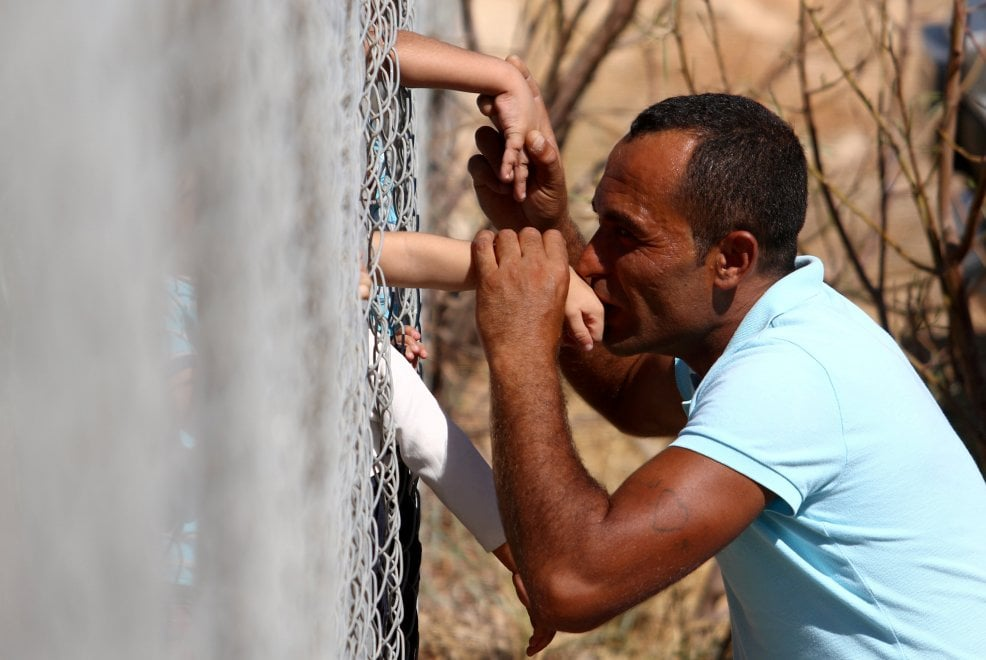 Cipro, papà siriano ritrova i figli in un campo rifugiati: il bacio attraverso il filo spinato