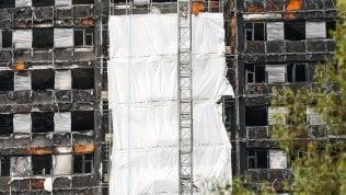 Londra copre la Grenfell Tower:a quattro mesi dal tragico rogotelo bianco sullo scheletro foto