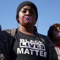Bocche coperte con la bandiera confederata per protestare al museo contro Trump