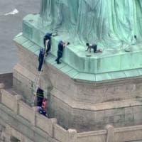 Donna scala la statua della libertà per protesta contro l'espulsione degli immigrati clandestini