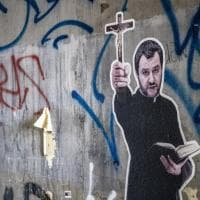 """Roma, spunta murale di Salvini con tonaca e crocifisso in mano. Sul bordo dell'opera la scritta """"Vattene, Satana"""""""