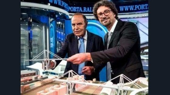 Toninelli da Vespa ride vicino al plastico del ponte Morandi. Sui social è polemica
