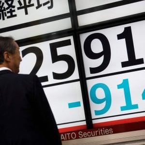 Un pedone davanti all'insegna dell'andamento della Borsa di Tokyo