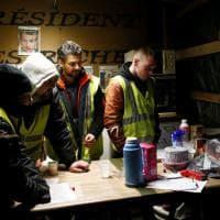 Sotto le tende, nei bar, sugli smartphone: i gilet gialli ascoltano il discorso di Macron