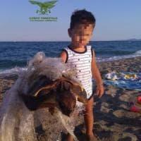 Sardegna, bimbo salva tartaruga intrappolata dalla plastica
