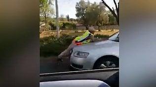 Prova a farle una multa, ragazza trascina via poliziotta con l'auto