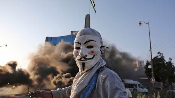 Proteste palestinesi: un manifestante con il volto di Guy Fawkes durante gli scontri con le forze israelinae, West Bank 11 novembre (Photo by ABBAS MOMANI / AFP)