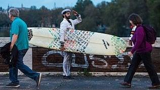 L'idea del comico romano contro il traffico: nel Tevere con il surf