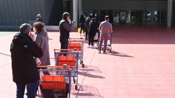 Cittadini in fila per la spesa in un supermercato