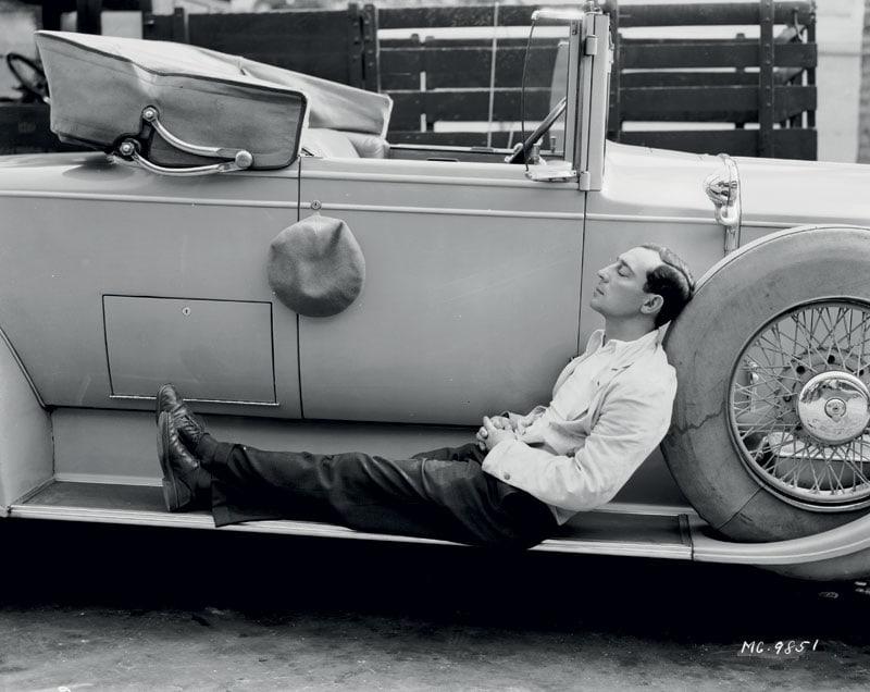 Il divo del cinema muto Buster Keaton in relax sul predellino di un'auto convertible (1930).