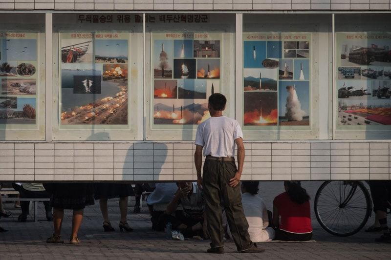 Un uomo guarda le immagini delle esercitazioni militari e lanci dei missili a Pyongyang