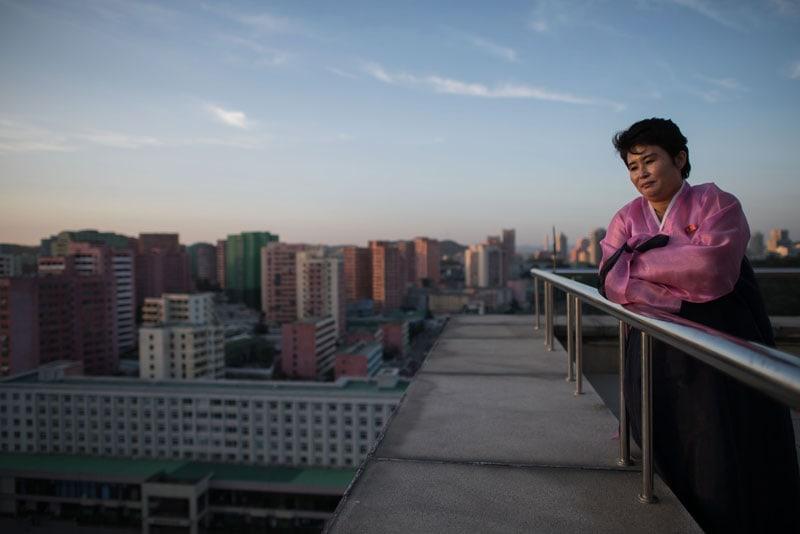 Una guida turistica davanti allo Skyline della città in cima all'Arco di Trionfo a Pyongyang