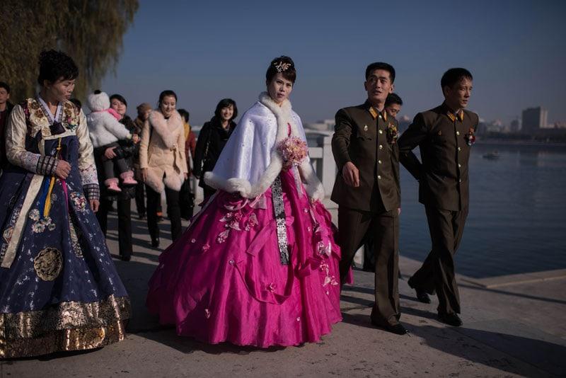 Una sposa, con i suoi amici e parenti, cammina sulle sponde del fiume Taedong a Pyongyang