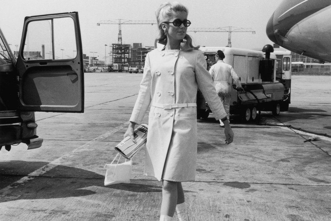 L'attrice Catherine Deneuve all'aeroporto di Londra con un cappotto disegnato da André Courrèges