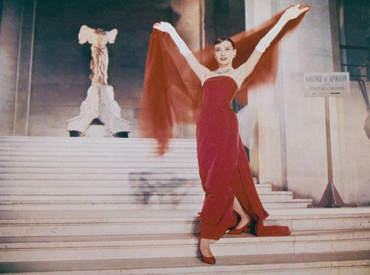 Audrey Hepburn sulla scala Daru del Louvre progettata da Hector Lefuel in una scena del film Cenerentola a Parigi del 1957. Sullo sfondo la statua della Nike di Samotracia
