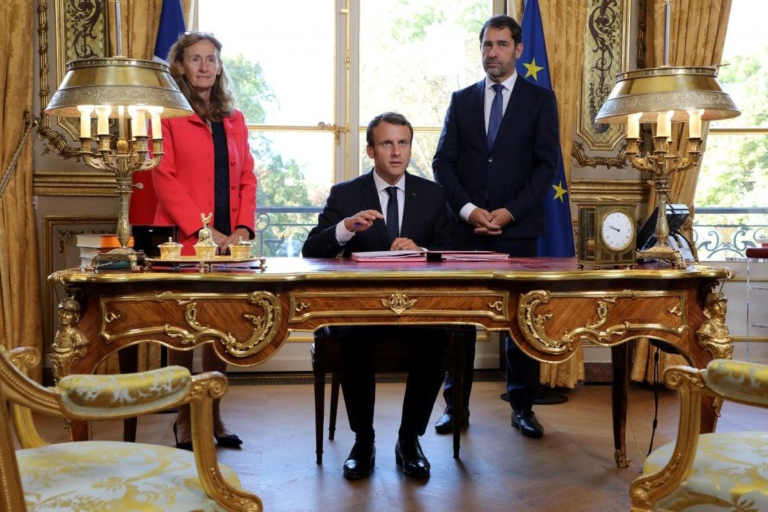 Il presidente francese Emmanuel Macron seduto alla sua scrivania