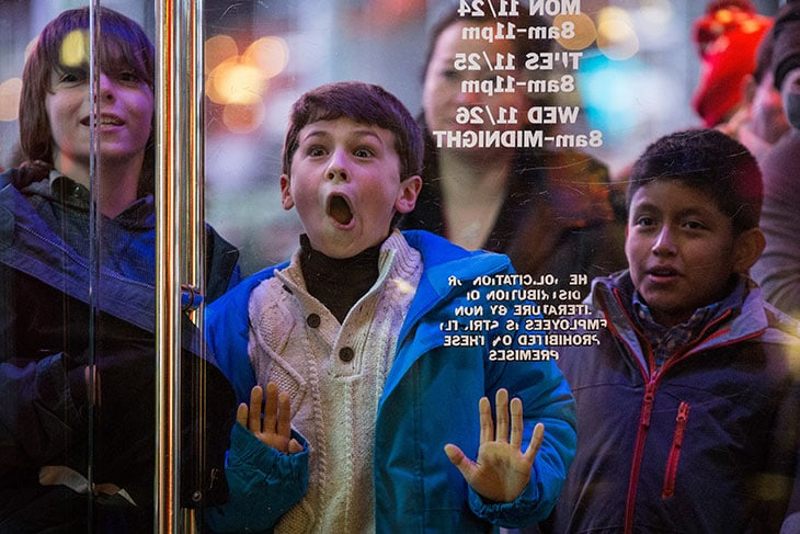 Un ragazzino estasiato mentre aspetta di entrare da Toys R Us in Times Square, New York, durante il Black Friday del 2014