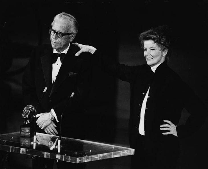 Katharine Hepburn e Lawrence Weingarten agli Oscar del 1974. L'attrice indossò un pigiama nero con giacca alla coreana.
