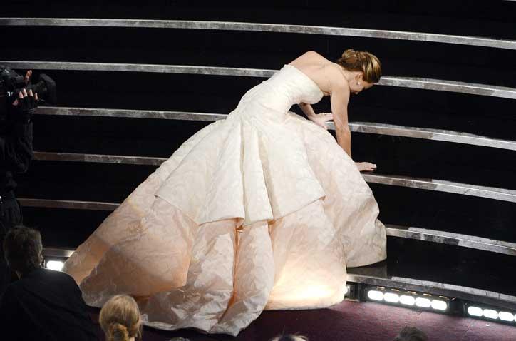Jennifer Lawrence cade salendo sul palco per ritirare l'Oscar