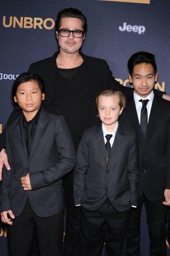 Brad Pitt con tre dei suoi figli: Pax, Maddox e Shiloh, che veste come i fratelli maschi e si sente a tutti gli effetti come loro