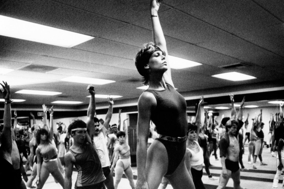 Jamie Lee Curtis nel film Perfect del 1985, periodo del boom dell'aerobica. Oggi il numero di chi pratica attività fisica è aumentato, ma lo è anche quello degli italiani in sovrappeso.