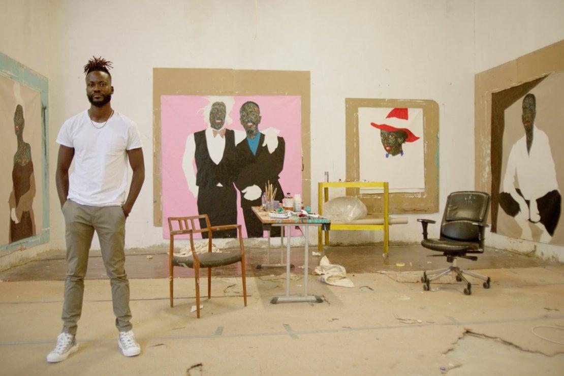 Amoako Boafo, protagonista del video di Dior Men, ritratto con alle spalle i suoi dipinti (ph. Chris Cunningham)