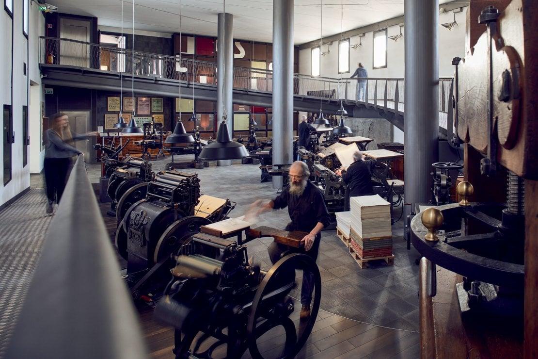 Il salone delle macchine da stampa: sullo sfondo, la parete-archivio dei caratteri in piombo e in primo piano una macchina da stampa a pedali azionata dal tipografo.