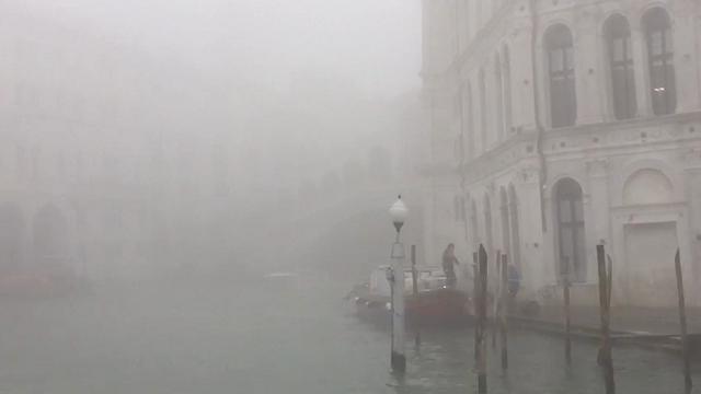 Venezia nella nebbia, le barche sotto il ponte di Rialto