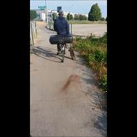 L'africano in bici che porta una nutria in mano