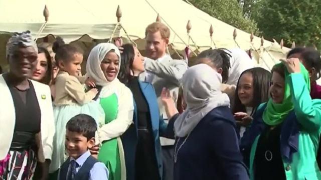 Il vento scompiglia i capelli di Meghan, il principe Harry l'aiuta con un gesto